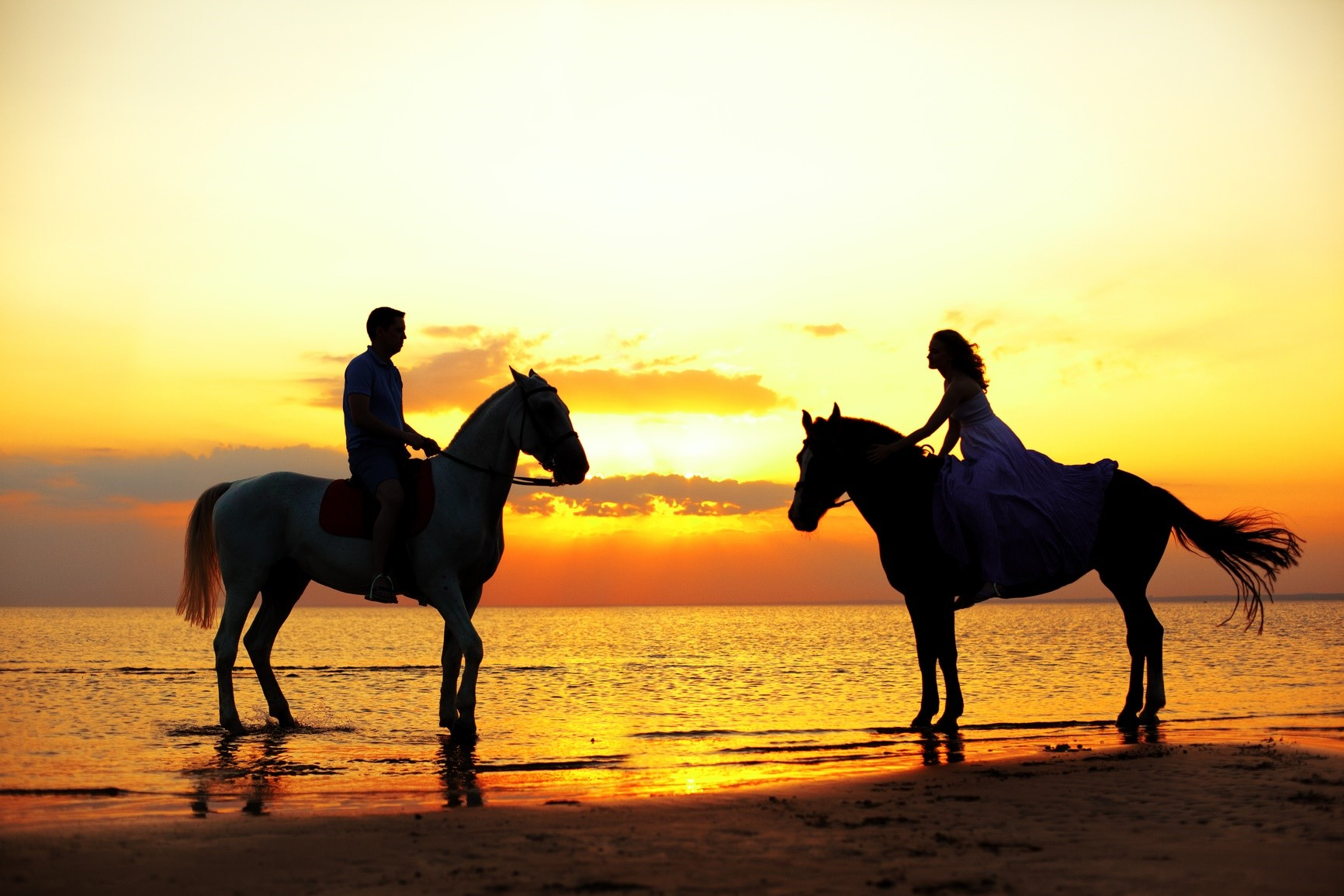 Horseback Riding - Two riders on horseback at sunset on the beach. Lovers ride horse